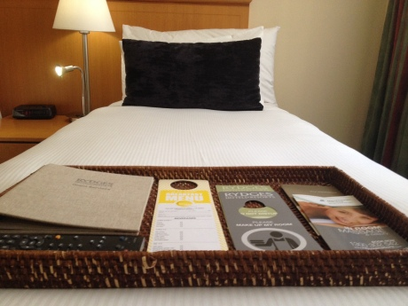 One of the single beds with a welcome information pack of the hotel